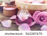 Stock photo essential oil with rose petals on wooden background 562287670