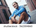 smiling tired athlete in blue... | Shutterstock . vector #562304860