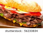 Large roast beef sandwich with cheese, lettuce, tomatoes, onion, red and yellow peppers. - stock photo