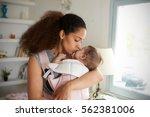 Mother Cuddling Baby Daughter...