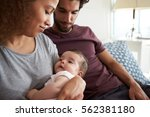 parents sitting on sofa... | Shutterstock . vector #562381180
