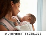 close up of mother cuddling... | Shutterstock . vector #562381318