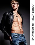 Small photo of Young handsome muscled fit male model man posing in studio showing his abdominal muscles in leather jacket