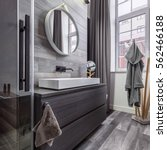 Small photo of Stylish wooden bathroom with round mirror and countertop basin