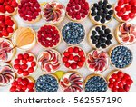 Fruit and berry tartlets dessert tray assorted top view background. Beautiful delicious tarts, bright, colorful pastry cakes sweets with fresh raspberries, figs, strawberry. French Bakery pattern.