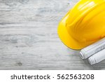 Small photo of Hard hat construction plans on wooden board building concept.