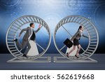 Stock photo business concept with pair running on hamster wheel 562619668