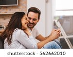 young happy couple sitting on... | Shutterstock . vector #562662010