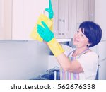 glad retiree woman cleaning... | Shutterstock . vector #562676338