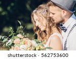 bride and groom hugging at the... | Shutterstock . vector #562753600