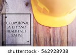 Small photo of Word OCCUPATIONAL SAFETY AND HEALTH ACT (OSHA) with yellow safety helmet on wooden base