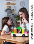 preschool teacher with cute girl | Shutterstock . vector #563026228