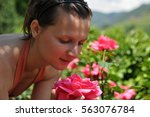 Stock photo beautiful young girl smelling a beautiful rose on a sunny day 563076784