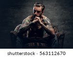 Small photo of The shirtless, tattooed bearded male sits on a chair over grey background.
