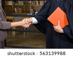 Small photo of Businesswoman shaking hands with lawyer in office