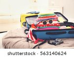 opened traveler case on bed | Shutterstock . vector #563140624