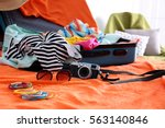open suitcase with clothes and...   Shutterstock . vector #563140846