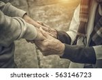 senior and young holding hands... | Shutterstock . vector #563146723