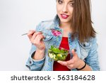 woman eating healthy salad from ... | Shutterstock . vector #563184628