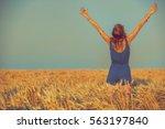 girl enjoying in a wheat field. | Shutterstock . vector #563197840