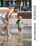 Man and boy toddler playing in fountains. - stock photo