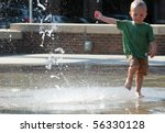 Boy toddler running across pavement with water squirting in the air. - stock photo