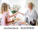 bride in silk robe clangs her... | Shutterstock . vector #563339830