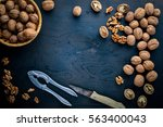 whole nuts on the wooden black... | Shutterstock . vector #563400043