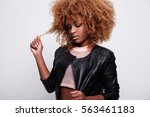 black woman toches her curly... | Shutterstock . vector #563461183