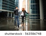couple having fun near puddle... | Shutterstock . vector #563586748