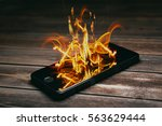 smartphone burning on wooden... | Shutterstock . vector #563629444
