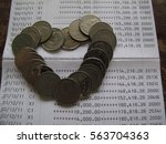 coin in heart shape on bank... | Shutterstock . vector #563704363