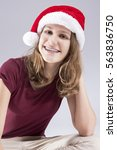 Small photo of Dental Concepts and Ideas. CHappy Caucasian Teenager in Santa Hat With Teeth Brackets. Sitting. Vertical Image Composition