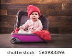 Stock photo cute baby in pink travel bag on wooden background 563983396