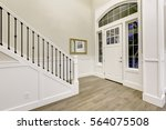 Small photo of Chic white entryway design accented with paneled walls, high ceiling, entrance door framed by transom windows, light gray hardwood floor and staircase. Northwest, USA
