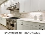 Stock photo gourmet kitchen features white shaker cabinets with marble countertops paired with stone subway 564076333