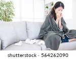 sick young woman sneeze at home ... | Shutterstock . vector #564262090