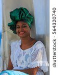 Small photo of SALVADOR, BAHIA, BRAZIL - JAN 25, 2017: : Farol nada Barra, Brazilian woman of African descent, smiling, dressed in traditional Baiana attire