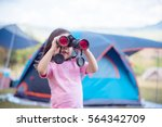 Small photo of little Asian girl wearing pink T-shirt uses binoculars to watch birds beside tent while camping with family.