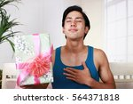 smiling man with a gift   Shutterstock . vector #564371818