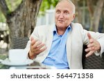 Small photo of Portrait of agitated mature man gesturing actively white having conversation with someone out of frame at outdoor cafe lounge on bright summer day