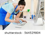 Young Woman Cleaning Keyboard...