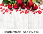 Stock photo red roses and greeting card on a wooden table 564547543