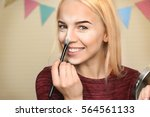 beautiful young woman applying... | Shutterstock . vector #564561133