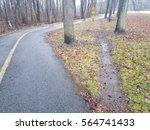 Small photo of curved asphalt bike trail with straight shortcut trail through the grass