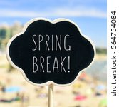 Small photo of closeup of a black signboard in the shape of a thought bubble with the text spring break written in it, in front of a blurred beach with many people bathing and sunbathing