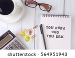 Small photo of YOU KNOW WHO YOU ARE text on notebook.coffee,calculator,pen,rubber stamp,glasses on the desk.top view.