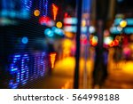 Small photo of Display of Stock market quotes with city scene reflect on glass