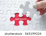 close up of girl's hand placing ... | Shutterstock . vector #565199224