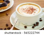 Small photo of cup of espresso coffee and coffee bean with donus on wooden table background